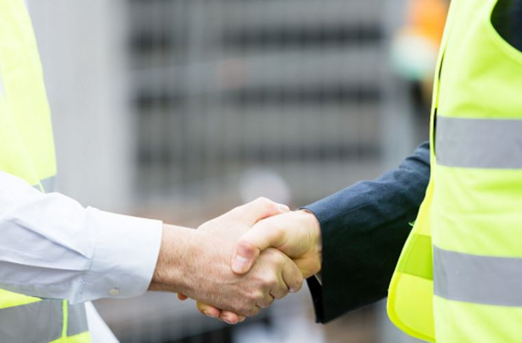 Contact us. Here is a handshake among construction workers.