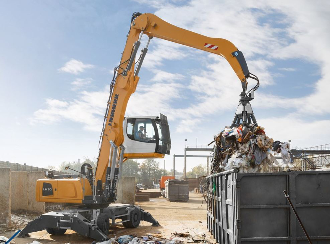 Liebherr material handler lifting scraps and waste from dumpster